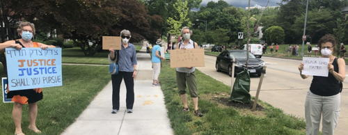 People with protest signs and masks lined up outside on sidewalk