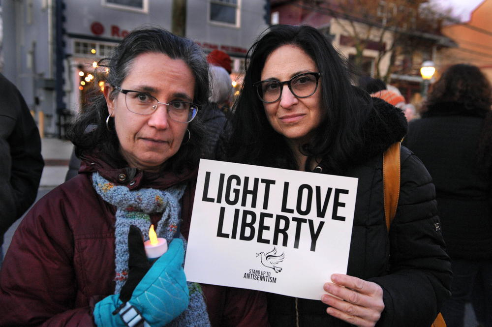 Two women  bundled up for cold weather with protest sign that says Light Love Liberty