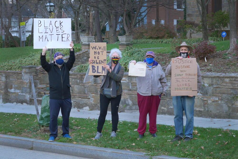 4 people on sidewalk holding Black lives matter protest signs